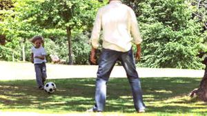Father and son in slow motion playing soccer