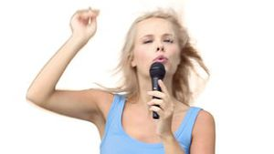 Woman pointing while singing with a microphone