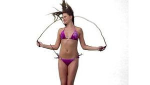 Woman playfully jumping over a skipping rope