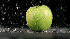 Water raining on an apple in super slow motion