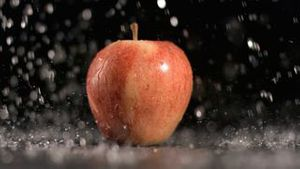 Water raining on apple in super slow motion