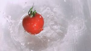 Tomato falling into water in super slow motion