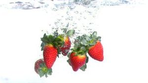 Strawberries dropped into water in super slow motion