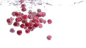Raspberries dropped into water in super slow motion