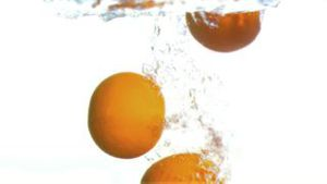Grapefruits dropped into water in super slow motion