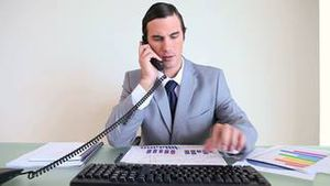 Businessman working while picking up the phone