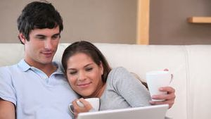 Couple sitting while looking at a laptop