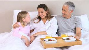 Smiling family sitting in a bed