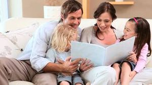 Smiling family reading a book together