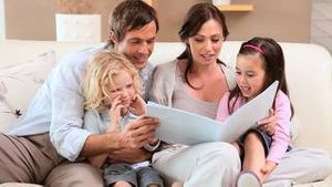 Smiling family reading a book