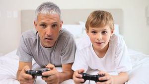 Smiling father and son playing video games