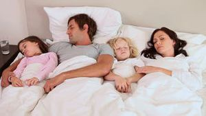 Family sleeping in a bed
