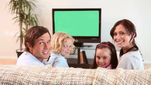 Family sitting while watching the television