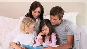 Children reading a book with their parents