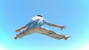 Man jumping in slow motion in the straddle position