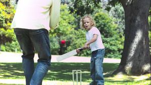 Father and son in slow motion playing cricket
