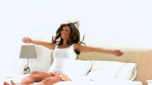Woman falling back on her bed in slow motion