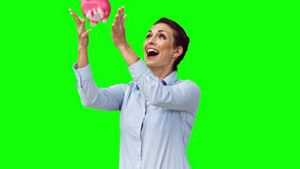 Happy woman in slow motion throwing a piggy bank