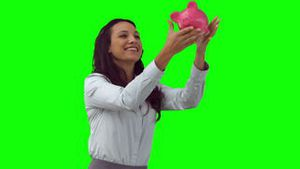 Brunette woman in slow motion throwing a piggy bank