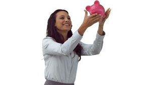 Happy brunette in slow motion catching a piggy bank