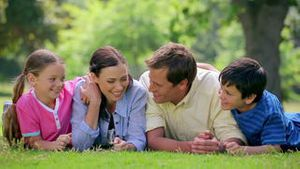 Happy family lying together on the grass