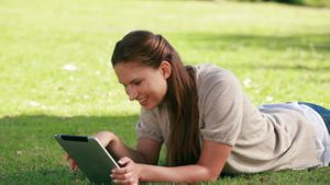 Woman using an eBook in a park