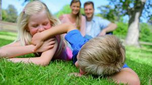 Brother and sister tickling each other while lying in the grass