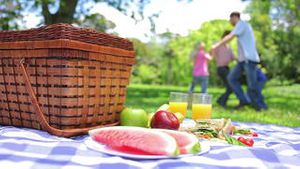 Family dancing in a ring in the background with a platter on a picnic basket in the foreground