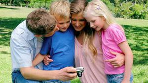Family smiling while looking at the photo gallery on their camera