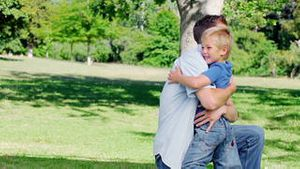 Father kneels on the grass before hugging his son who runs to him