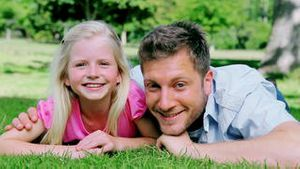 Man looks at his daughter with a confused look before smiling as they lie on the grass