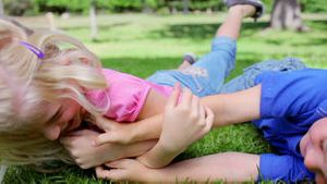 Boy and a girl tickling each other on the grass