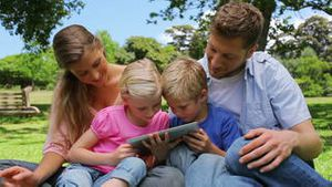 A family reads a book as they sit together in a park before looking at the camera