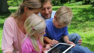 A boy sits with his family who watches as he presses the screen of a tablet pc