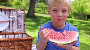A boy looks at the camera while biting a watermelon before swallowing and smiling