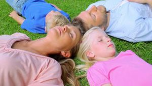 A family lies head to head in grass while sleeping before the daughter begins to move