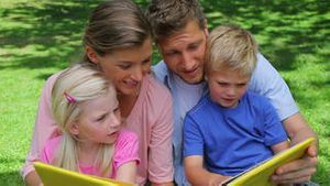 A family talking to each other while reading a book before looking at the camera and smiling