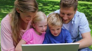 A family sitting together as they use a laptop before looking at the camera and smiling