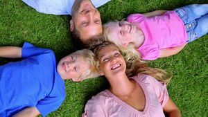 Overhead shot of a family smiling as they lie head to head in grass