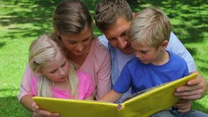 Family reading a book while sitting together before looking at the camera while turning the page