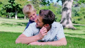 Father looking ahead while lying on the grass before his son peeks his head out from behind him