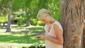 A woman standing by a tree looking at her mobile phone