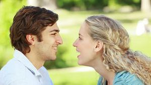 A couple look at each other as they kiss in the park and then look at the camera