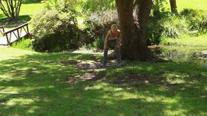 A woman jogs in the park as she stops by a tree and moves soon after