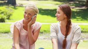 Two girls sit in the park and pass the phone back and forth while talking on it
