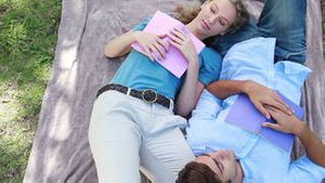 A couple sleep beside each other with books in the park