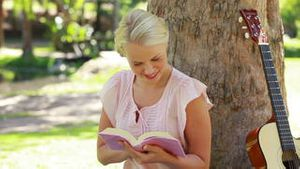 A woman sits by a tree reading as she looks at the camera
