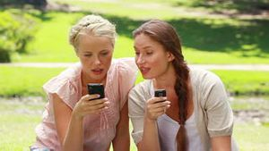 Two women on mobile phones in the park as they look at one of them in shock