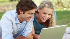 A smiling couple lie in the park with a laptop as they look up into the camera