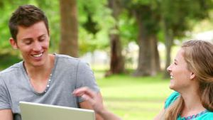 Woman laughing as she watches a laptop with her friend before playfully pushing him